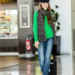 Young female passenger at the airport with suitcase — Stock Photo #39058659