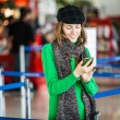 Young female passenger at the airport using her smart phone — Stock Photo
