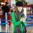 Young female passenger at the airport using her smart phone — Stock Photo #39058665
