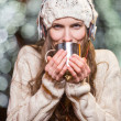 Young woman with headphones and hot tea outdoors in winter — Stock Photo