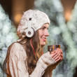 Cute teenage woman with headphones outdoor in winter — Stock Photo