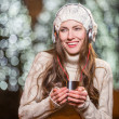 Young happy woman with headphones outdoor in winter — Stock Photo