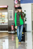 Young female passenger at the airport with suitcase — Stock Photo
