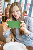 Woman using cell phone while sitting in a cafe — Stock Photo