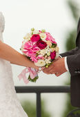 Wedding hands with bridal bouquet — Stock Photo
