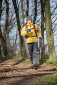 Mujer que camina cruz país sendero en el bosque — Foto de Stock