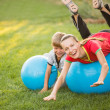 Mother and son having fun outdoors with sport gym ball — Stock Photo
