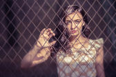 Woman behind wired fence — Stock Photo