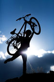Woman with bike over sunset — Stock Photo
