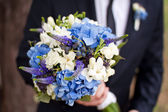 Bridegroom with beautiful wedding flowers — Stock Photo