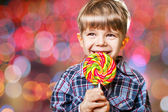 Boy having fun licking lollipop — Stock Photo