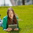 Stock Photo: Young womusing tablet outdoor