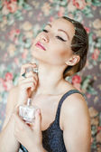 Beautiful woman smelling her perfume — Stock Photo