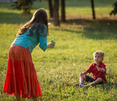 Happy family blowing bubbles in the park — Stock Photo