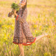 Beautiful smiling woman in a field at sunset — Stock Photo