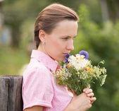 молодая женщина с цветами над естественный фон — Стоковое фото