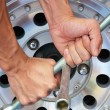 The strong hand try to remove the nut of wheel  — Stock Photo