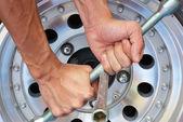 Güçlü el denemek tekerlek fındık kaldırmak için — Stok fotoğraf