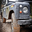 Old Land Rover Defender in the mud - Stock Photo
