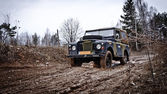 Old Land Rover Defender driving in the mud — Stock Photo