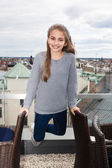 The happy young girl against city roofs — Stock Photo
