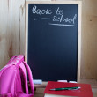 Back to school. Blackboard with easel with text and books — Stock Photo