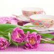 Pink tulips with cups of tea and chocolates isolated — Stockfoto