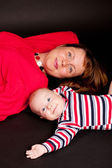 Happy mother and baby boy on black background — Stock Photo