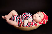 Little boyin a plate on black background — Stock Photo