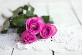 Pink rose on wood table with vintage napkin — Stock Photo
