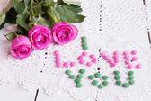 ビンテージ ナプキンの色キャンディーとピンクのバラ — ストック写真