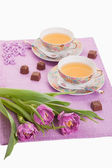 Violet tulips with cups of tea and chocolates — Stock Photo
