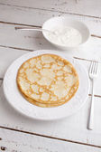 Homemade pancakes pancakes on a plate with sour cream on wood ta — Stock Photo