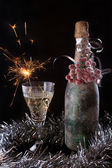 Bottle decorating berries with glass and sparklers — Stock Photo
