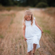 Happy running girl on a oat field — Stockfoto