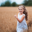 Happy running girl on a oat field — Stock Photo