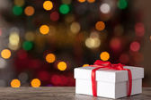 White box with a ribbon on background bokeh — Stock Photo
