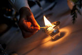 Hand igniting candle — ストック写真