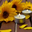 Decorative composition of yellow flowers and little candles — Stock Photo