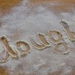 Background with word dough in scattering flour on wooden table — Stock Photo #24774355