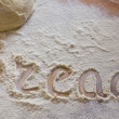 Background with word bread in scattering flour on wooden table — Stock Photo #24774689