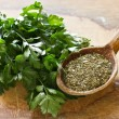 Fresh  and dry parsley on wooden background — Stock Photo