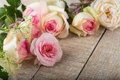 Fresh roses on wooden background — Stock Photo