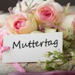 Postcard with elegant flowers and tag with word Muttertag — Stock Photo