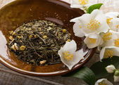 Dry herbal tea with jasmine on plate — Stock Photo