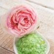 Sea salt in bowl with rose on wooden background — Stok fotoğraf