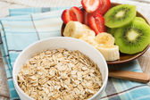 Oat flakes in bowl with fruit — Stock Photo