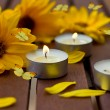 Decorative composition of yellow flowers and little candles — Stock Photo #27668215