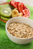 Oat flakes in bowl with banana and strawberry — Stock Photo