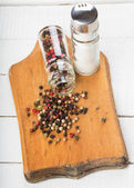 Mixed pepper and salt on wooden board — Stock Photo